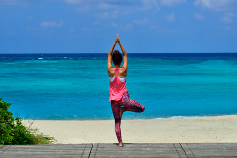 a lady striking a yoga pose on the beach