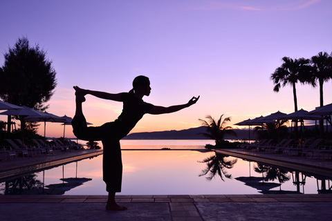 a lady holding a yoga pose in front of the swimming pool