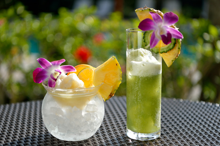 glasses of frozen cocktail with flowers and slices of pinapple